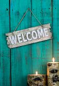 picture of quaint  - Wood welcome sign by burning log candles hanging on antique green distressed background - JPG