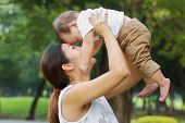 stock photo of kiddie  - Asian family Mother holding her baby was laughing in park - JPG