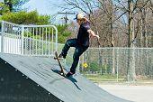 pic of skateboarding  - Action shot of a skateboarder on a skateboarding ramp at the skate park - JPG