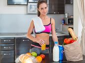 stock photo of cold-shoulder  - Pretty attractive athletic sportive lady woman standing in kitchen with a towel on her shoulder and healthy food fresh fruits milk bread around drinking cold drink beverage - JPG
