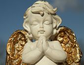 stock photo of little angel  - praying little angel figure with golden wings isolated on sky - JPG