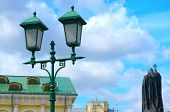 foto of priest  - Streetlight against the blue sky and a monument to the priest - JPG