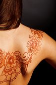 stock photo of henna tattoo  - naked back of young girl with henna tattoo mehendi on dark backround - JPG