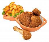 image of southern fried chicken  - Cooked southern fried chicken portions and potato wedges in bowls isolated on a white background  - JPG