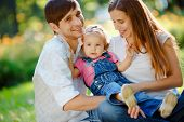 picture of three life  - Happy family of three people relaxing in a city park - JPG