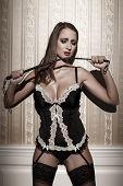 image of bdsm  - Sensual brunette woman in underwear holding whip at night bdsm - JPG