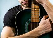 picture of acoustic guitar  - guitarist holding an acoustic guitar on a light background - JPG