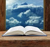 stock photo of bible story  - Bible open on a table top with stormy sky view at window - JPG