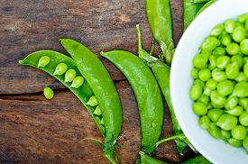 picture of pea  - hearthy fresh green peas over a rustic wood table - JPG