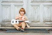stock photo of ukulele  - Little happy boy plays his guitar or ukulele - JPG