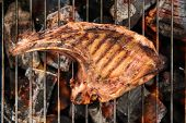 stock photo of flame-grilled  - Grilled pork steaks over flames on the grill - JPG