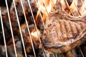 foto of flame-grilled  - Grilled pork steaks over flames on the grill - JPG