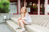 foto of pullovers  - Outdoor portrait of a cute little girl in a city - JPG