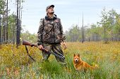 stock photo of swamps  - hunter with gun and dog on the swamp - JPG