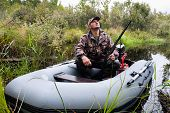 picture of hunter  - Hunter sitting in a motor boat on the river - JPG