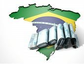 picture of brazilian money  - The shape of the country of Brazil in the colours of its national flag recessed into an isolated white surface with a wad of folded Brazilian real notes resting on it - JPG