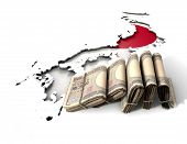 pic of japanese flag  - The shape of the country of Japan in the colours of its national flag recessed into an isolated white surface with a wad of folded japanese yen notes resting on it - JPG