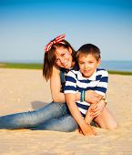 picture of little sister  - Portrait of happy teen sister and little brother on the beach - JPG