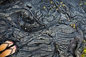 stock photo of big-foot  - Black and ropy Pahoehoe lava with female feet in the corner on Big Island in Hawaii.