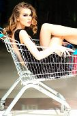 pic of trolley  - One misterious fashion woman in black dress sitting in shopping trolley indoor on shop background vertical picture - JPG