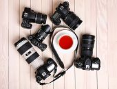 stock photo of megapixel  - Modern cameras with cup of tea on wooden table - JPG