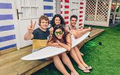picture of beach hut  - Group of funny young friends holding a woman on top of surfboard in a summer day over a beach striped huts background - JPG