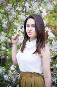 picture of magnolia  - pretty girl holding a sprig of flowering magnolias - JPG