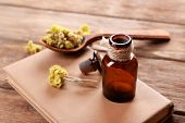 picture of roughage  - Old book with dry flowers and bottle on table close up - JPG