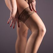 Постер, плакат: The Woman Wears A Nylon Stocking On Slender Leg