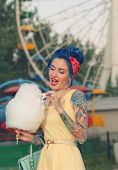 stock photo of candy cotton  - Girl with a tattoo with cotton candy in the hands of an amusement park on the background of traits kolesa - JPG
