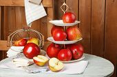 pic of serving tray  - Tasty ripe apples on serving tray on table on wooden background - JPG