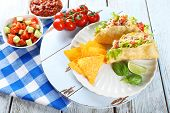 pic of tacos  - Tasty taco with nachos chips and vegetables on plate on table close up - JPG