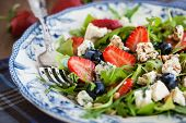 image of pine nut  - Fresh delicious arugula strawberry blueberry pine nuts and blue cheese salad soft focus
