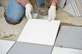 image of ceramic tile  - Worker installs ceramic tiles on a floor - JPG