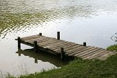 stock photo of jetties  - Very old wooden jetty at a peaceful fishing lake side - JPG