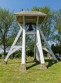 pic of graveyard  - Bells on graveyard with gravestones in Mirns in province Friesland near Lemmer The Netherlands image Daan Kloeg Commee - JPG
