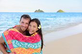 stock photo of bathing  - Swimming romantic couple wrapped in bathing towel on beach - JPG