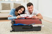 foto of boarding pass  - Portrait Of Happy Young Couple Packing Luggage Showing Boarding Pass - JPG