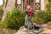 pic of beast-man  - Little boy plays near a statue of a dragon - JPG