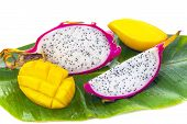 picture of dragon fruit  - Dragon fruit and papaya on banana leaf against white background - JPG