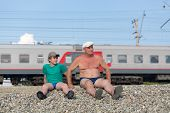 stock photo of grandfather  - grandfather and grandson sitting on the railway embankment - JPG