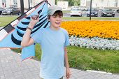 picture of post-teen  - boy gets ready to launch a kite - JPG