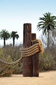 stock photo of dock  - Old wooden docking post with nautical rope in sand and surrounded by palm trees - JPG