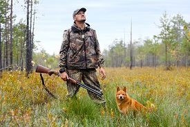 picture of hunter  - hunter with gun and dog on the swamp - JPG