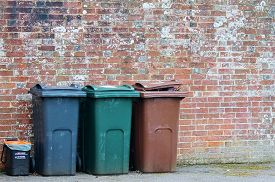 stock photo of dustbin  - Trash can dustbins outside against brick wall