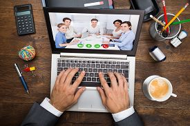 stock photo of chat  - Businessman In Video Chatting With His Colleagues On Laptop - JPG