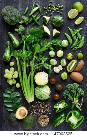 Spread of fresh green produce on dark rustic distressed background, broccoli, celery, beans, capsicu
