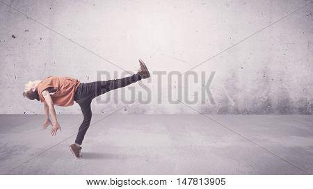 A beautiful young hip hop dancer dancing contemporary urban street dance in empty clear grey wall ba