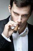 stock photo of hustler  - A young man looking suspicious with a cigar - JPG