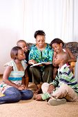picture of girl reading book  - a happy african mother reading a book to her 4 children in living room - JPG